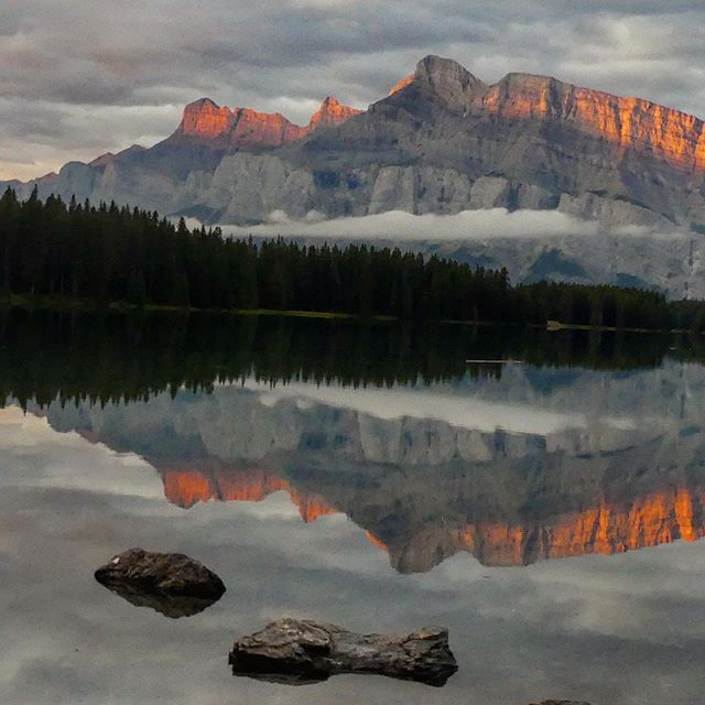 Happiness is catching the first rays of sunlight on a mountaintop!😎 #sunrise #sunrise_shotz #rockymountains #reflection #naturephotography #nature_perfection #earthoutdoors #travelalberta #explorebanff #pocket_allnature #oh_canada_ #canadianrockies #enrouteplaceoftheday