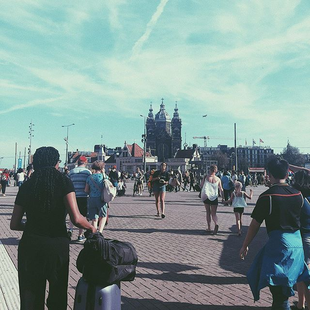 After taking the pic, I realised that the woman with the purple suitcase, actually looked like me from the back 🗿#amsterdam#travels#instatravel#potd#instadaily#amsterdamcentraal#trainstation#blueskies#hotweather#instapic#holiday#pictures#clone#architecture